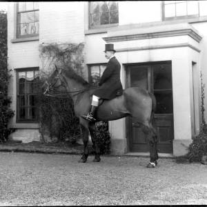 G36-179-14 Man mounted on horse outside house.jpg