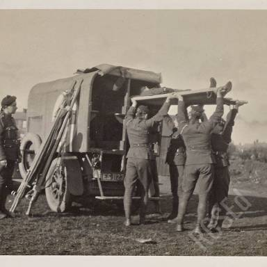 Loading wounded into motor ambulance under direction of Corporal Anderson