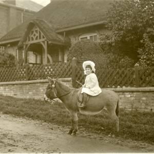 G36-009-08 Girl on donkey outside house.jpg