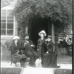 G36-022-08 Man with beard and lady seated with two girls, a dog and a cat under a jasmine-covered porch.jpg