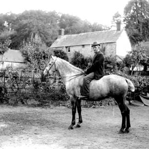 G36-244-15 A farmer mounted on a horse in front of house.jpg