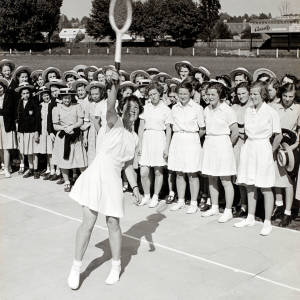 Woman demonstrates tennis to schoolgirls