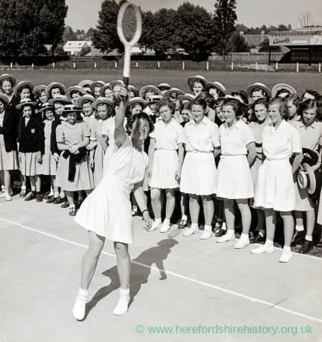 Woman demonstrates tennis to schoolgirls