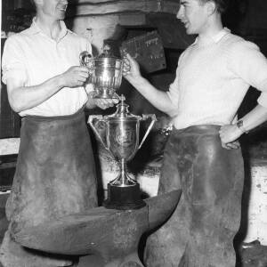 Two blacksmiths with trophies.