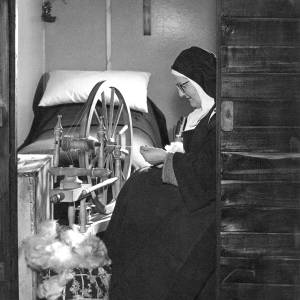 A nun from the Poor Clare's spins wool in her cell