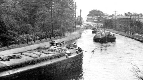 Barges on tow through Lymm Vilage