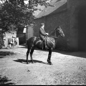 G36-300-04 Young lad seated on horse in a cobbled courtyard.jpg