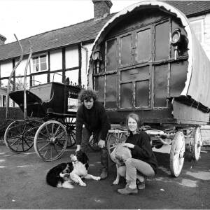 A man and woman with a gypsy caravan.