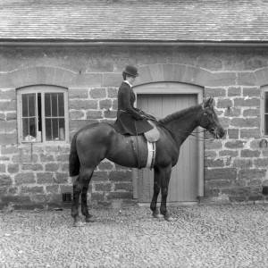 G36-246-01 Lady seated side-saddle on a horse in stable yard.jpg