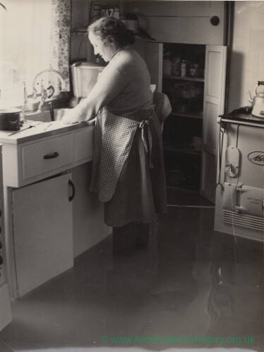 A lady washing up in a flooded kitchen.