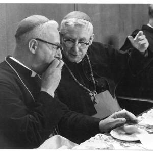 232 - Two Roman Catholic clerics talking at a table