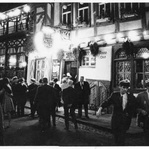 265 - German Wein Haus in the evening and people walking in front