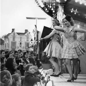 Crowds watching dancers/paraders on the front of Mrs Price's show at Hereford May Fair, 1950s.