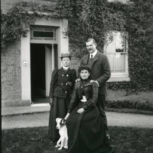 G36-025-08 Seated lady, standing lady and man with dog in front of house.jpg