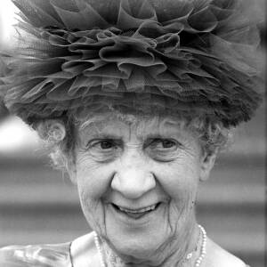 An elderly lady wearing a distinctive hat.
