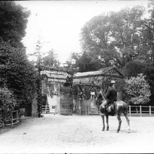 G36-065-01 'Health and happiness to our squire and his bride' banner over entrance gates, Ledbury Lodge, Stoke Edith with lodge and bowler-hatted man on horse.jpg