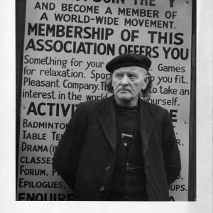 """403 - Man wearing beret standing in front of poster - 'Why not join the """"Y""""'"""
