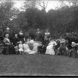 G36-307-01  12 adults, child on toy horse and baby in a garden family group of 4 generations.jpg