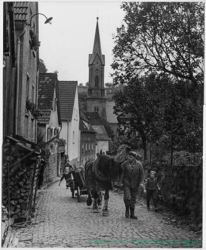 112 - Man leading horse and cart up cobbled street, with children alongside