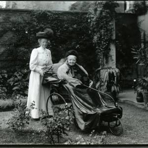 G36-011-04 DuBuisson; 31 Castle St Hereford; Lady pushing older lady in bath chair.jpg