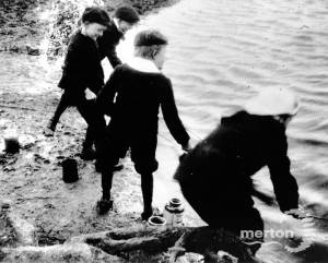 Young boys fishing for tiddlers with jam jars