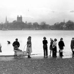Group of children at the edge of flooded playing field