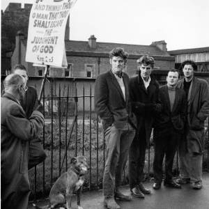 Group of men - and a dog - at a demonstration.