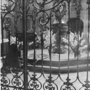 260 - Nun arranging flowers in church, picture taken outside railings