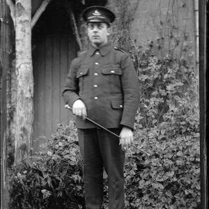 Soldier with swagger stick outside house