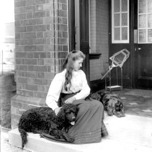 G36-323-14 Young lady with two dogs in doorway [as G36-323-12].jpg