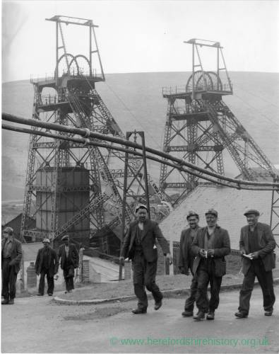 Group of miners leaving the pit. Good detail of colliery in background