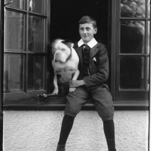 G36-032-04 Older boy in knickerbockers sitting in windowsill with bulldog.jpg