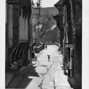 487 - Street scene looking over bridge, girl carrying dog