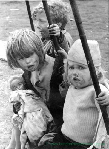 Three children play on a swing