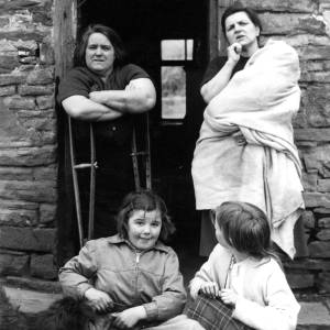 Two mothers with children and a dog outside stone house.
