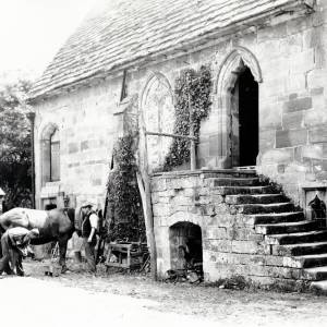 Brinsop Court with man shoeing horse