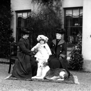 G36-545-12 Two ladies, a small child and a dog, in front of a house.jpg