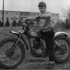 A young boy astride a motorcycle.