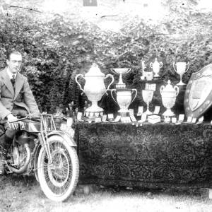 G36-502-13 Man on a motor cycle beside a table with much silverware.jpg
