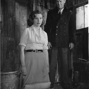 131 - John Mills and a woman in a wooden hut