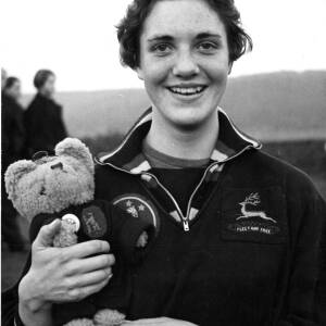 A female Birchfield Harrier athlete holding a teddy bear.
