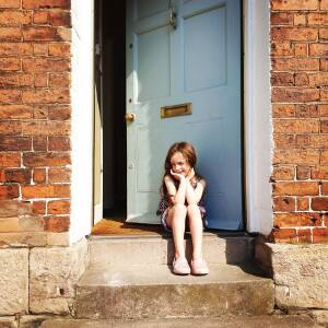 Child sitting on doorstep, St. Martin's St., Hereford, 25 April 2020