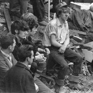 Group of young men sitting amongst rubble. (possible Aberfan aftermath?)