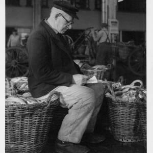483 - Man sitting on fish basket and writing