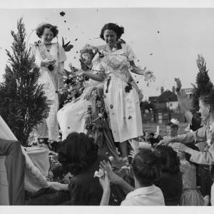402 - Three young women on float wearing floral princess sashes