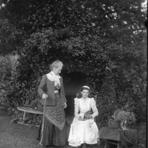 G36-225-05 Lady holding a garden fork, and a seated lady holding a kitten, in a garden.jpg