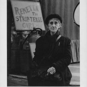 433 - Old woman sitting in front of sign for Strip-Tease girl Renetta