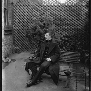 G36-034-08 KSLI Soldier as G36-034-04 in same setting but seated on a bench, next to a curious three legged circular metal chair.jpg