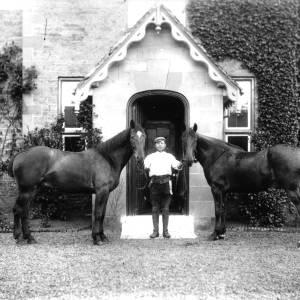 G36-326-12 Man holding two horses outside porch.jpg