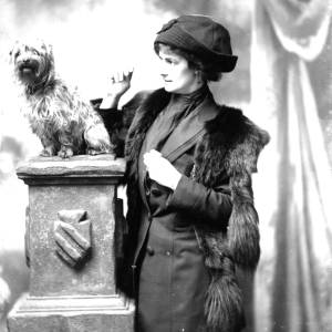 G36-150-06 Portrait of lady standing  beside small dog on pillar.jpg